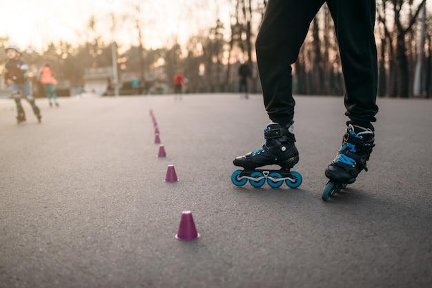 Gambe di pattinatore a rotelle in pattini sulla passerella di asfalto nel parco cittadino. tempo libero pattinatore maschile