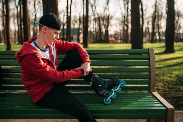 Pattinatore a rotelle in posa sulla panchina nei pattini, parco cittadino. tempo libero maschile rollerskater nel parco cittadino