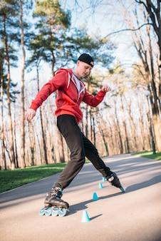 Pattinatore a rotelle, esercizio di trucco nel parco. tempo libero pattinatore maschile