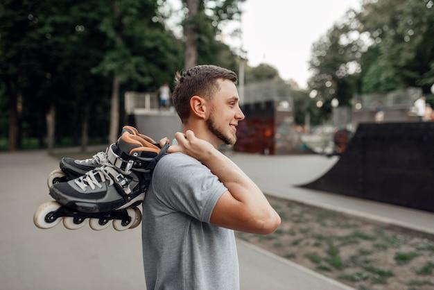 Pattinaggio a rotelle, pattinatore maschio porta i pattini sulla spalla, vista posteriore. pattinaggio urbano, sport estremi attivi all'aperto, tempo libero per giovani, pattinaggio a rotelle