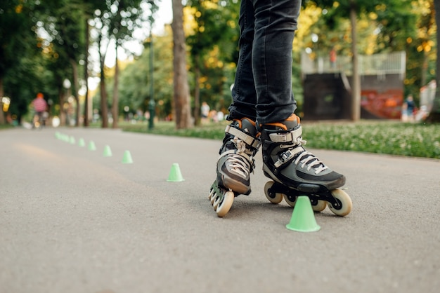 Pattinaggio a rotelle, pattinatore maschio che rotola intorno ai coni nel parco. pattinaggio urbano, sport estremi attivi all'aperto, tempo libero per giovani, pattinaggio a rotelle
