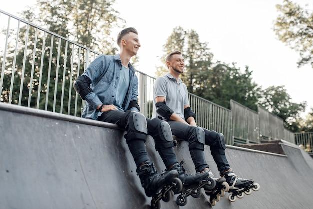 Pattinaggio a rotelle, due pattinatori maschii che si siedono sulla rampa nel parco.