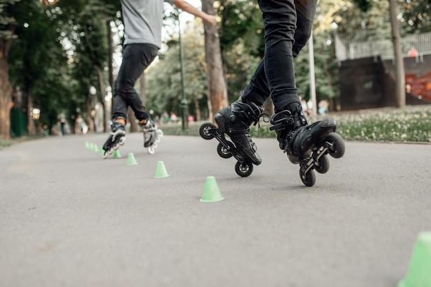 Pattinaggio a rotelle, due pattinatori che rotolano intorno ai coni nel parco. pattinaggio urbano, sport estremi attivi all'aperto, tempo libero per giovani, pattinaggio a rotelle