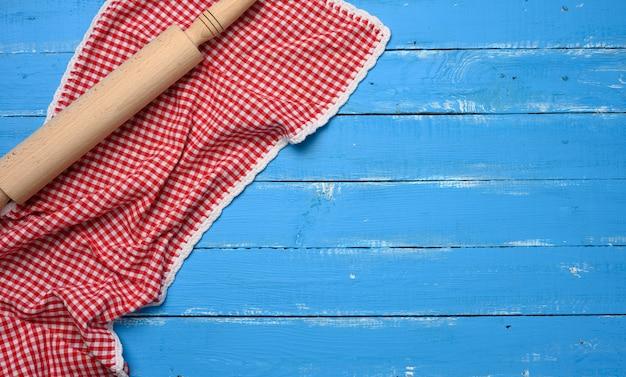Mattarello e tovagliolo da cucina in cotone rosso e bianco piegato su uno sfondo blu in legno, vista dall'alto, spazio copia