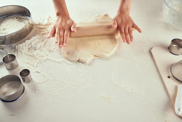 Rotolare la pasta sul tavolo prodotti di farina lavoro in cucina