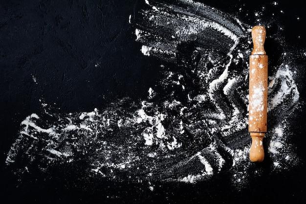 Mattarello con farina su fondo di cottura nero scuro, vista dall'alto, copia spazio per testo, menu, ricetta. disposizione piatta.