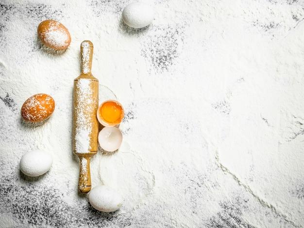 Mattarello con uova fresche sulla farina.