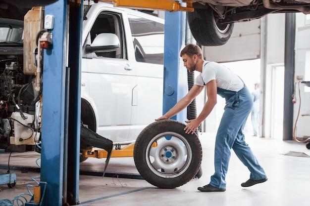 Pneumatico rotolante. l'impiegato con l'uniforme di colore blu lavora nel salone dell'automobile.
