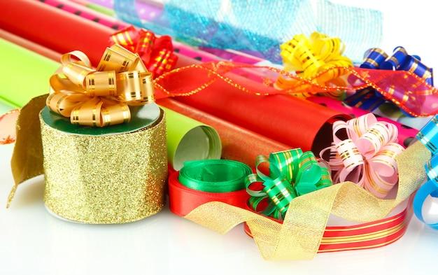 Rotoli di carta da regalo natalizia con nastri, fiocchi isolati su bianco