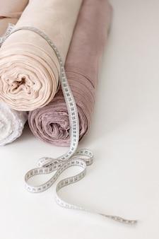 Rotoli di stoffa con un pollice sul tavolo bianco. sarta