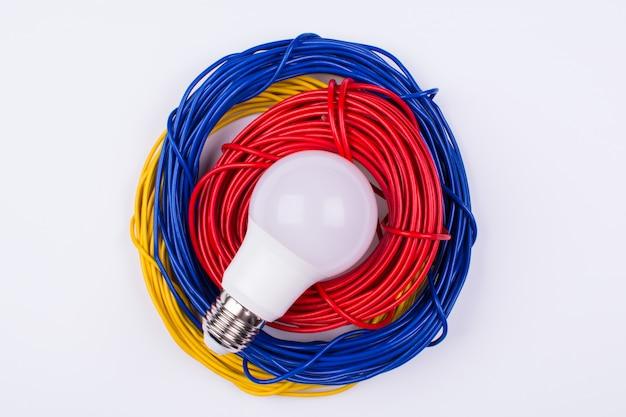 Rotoli di fili elettrici e una lampadina
