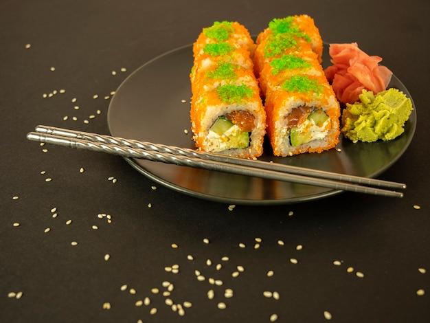 Involtini di pesce e cetriolo in caviale arancione, su un piatto grigio, uno sfondo nero e sparsi con semi di sesamo