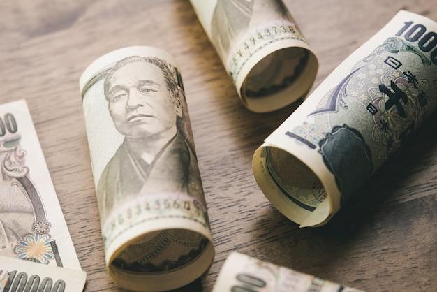 Rotoli delle banconote dei soldi di yen giapponesi sulla tavola di legno