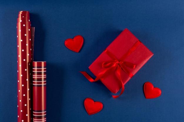 Rotoli di carta da imballaggio rossa e confezione regalo su sfondo di colore blu classico 2020 di tendenza. preparazione del concetto di imballaggio di san valentino 14 febbraio. disposizione piatta, sopra.