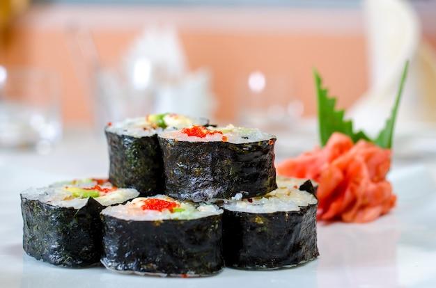 Panini, sushi e zenzero su un piatto bianco e una superficie chiara.