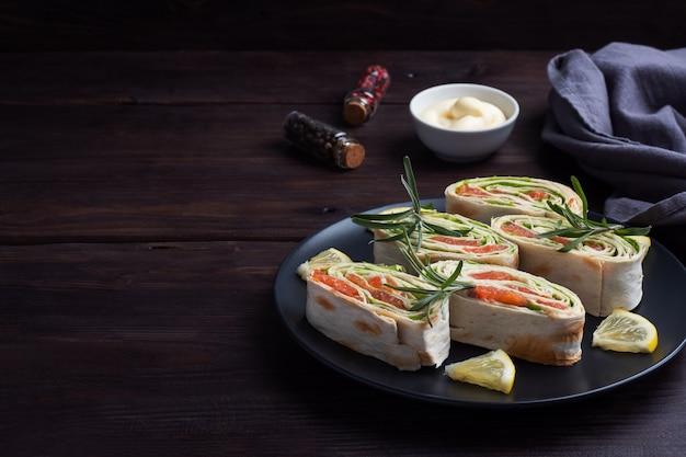 Rotoli di pane pita sottile e salmone rosso salato con foglie di lattuga su un piatto di ceramica nera