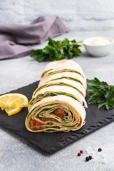 Rotoli di pane pita sottile e salmone rosso salato con foglie di lattuga