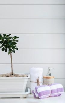 Rotoli di asciugamani bianchi e viola legati con corda di canapa sul tavolo bianco white