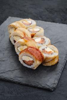 Rotoli con anguilla e crema di formaggio su lastra di ardesia