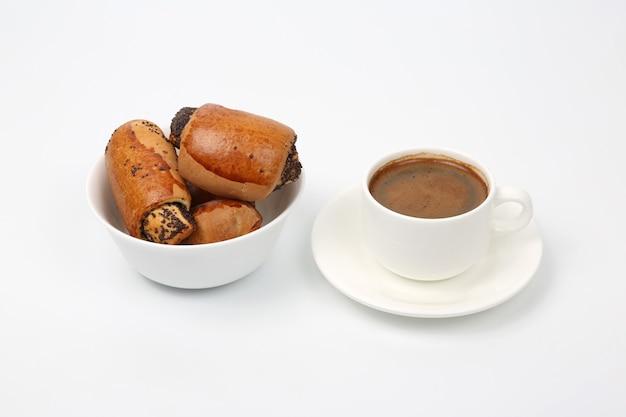 Involtini con semi di papavero e tazzina di caffè nero bianco