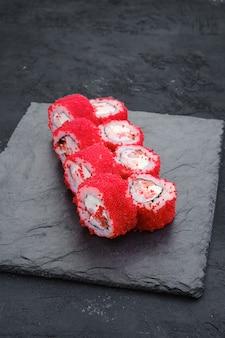 Involtini con gamberi e uova di pesce volante su lastra di ardesia