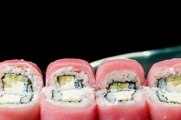 Rotoli con tonno, avocado, cetriolo, crema di formaggio, primo piano nori. cucina tradizionale giapponese.