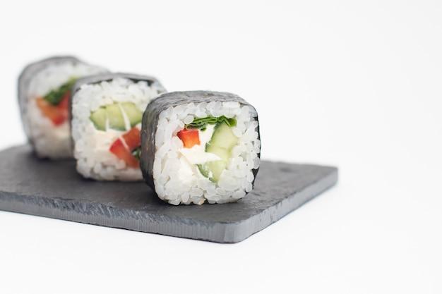 Gli involtini con le verdure vengono serviti su una tavola di ardesia nera.