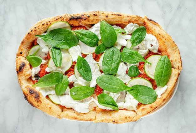 Pizza romana con spinaci, zucchine a fettine, stracciatella e pomodorini su superficie di marmo
