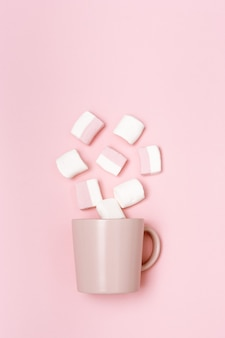 Concetto di vacanza romantica, tazza o tazza rosa e marshmallow, immagine monocromatica rosa pastello, vista dall'alto con lo spazio della copia