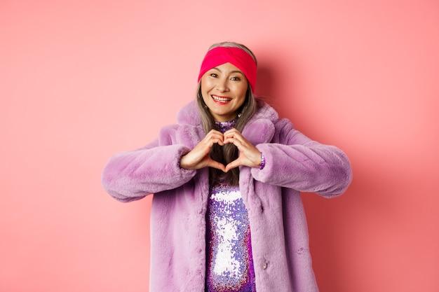 Romanticismo e san valentino. felice donna anziana asiatica che mostra il segno del cuore, ti amo gesto, sorridente e guardando la telecamera premurosa, in piedi in pelliccia sintetica, sfondo rosa.