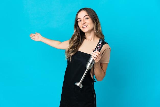 Donna rumena che utilizza il frullatore a immersione isolato sulla parete blu che estende le mani a lato per invitare a venire