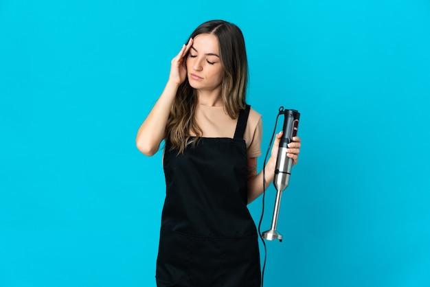 Donna rumena utilizzando frullatore a immersione isolato sulla parete blu con mal di testa