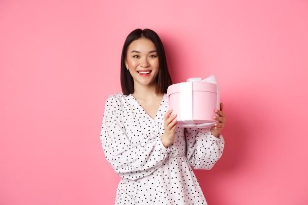 Romantica donna asiatica in abito carino tenendo la scatola con regalo, sorridendo felice a porte chiuse, in piedi con presente sul rosa