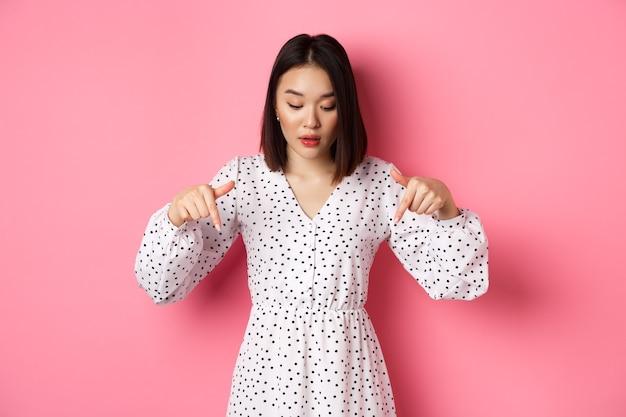 Romantica donna asiatica che sbircia in basso, punta le dita in basso, sembra curiosa per lo sconto del prodotto, in piedi su sfondo rosa