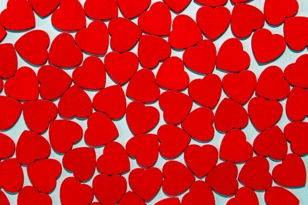 Sfondo romantico di tanti piccoli cuori rossi pattern. composizione di san valentino. concetto di amore.