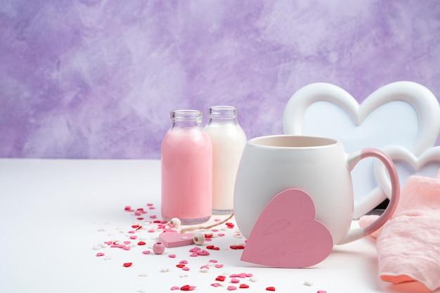 Sfondo romantico con un cuore rosa su una tazza da caffè, cornice bianca, latte e cuori su un bianco e