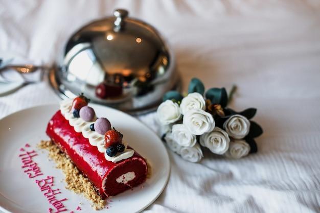 Torta di compleanno romantica sul letto con secchiello di fiori di rosa bianca