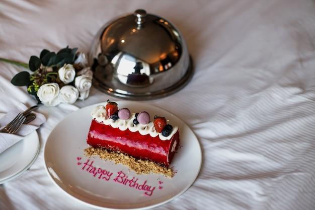 Torta di compleanno romantica con rosa bianca sul letto