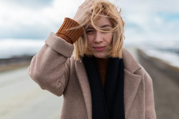 Romantica ragazza bionda in cappotto beige e sciarpa nera si trova su un'autostrada vuota sullo sfondo di prati innevati.