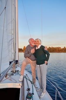 Romantico tour in barca per tutta la lunghezza di una coppia anziana felice che si tiene per mano e si abbraccia mentre sta in piedi sopra