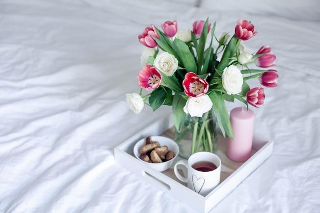 Romantica colazione a letto. mazzo di fiori. rose e tulipani.