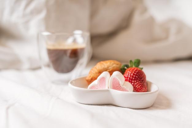 Prima colazione romantica a letto con fragole e caffè