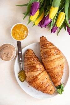 Romantica colazione con croissant croccanti, crema di marmellata al cioccolato, caffè e tulipani colorati