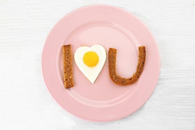 Colazione romantica con uova al sole sul tavolo