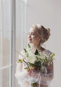 Sposa romantica con bouquet da sposa vicino alla finestra in attesa dello sposo