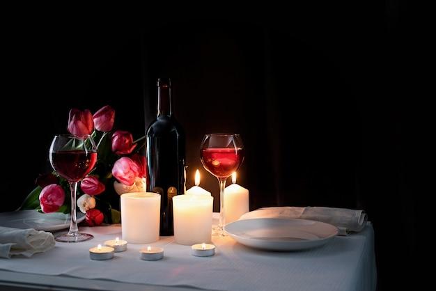 Cena romantica a lume di candela con vino, candele e bouquet di tulipani