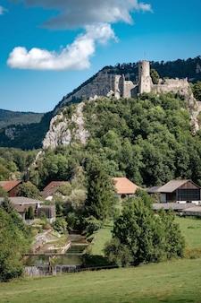 Castello romantico in cima a una collina in una valle montuosa nelle alpi della svizzera con un cielo azzurro sullo sfondo, piccolo villaggio sotto la roccia