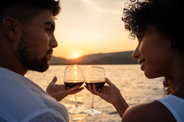 Primo piano romantico di un brindisi di coppia di razza mista con bicchieri di vino rosso attraversato dalla luce del sole al tramonto su un lago