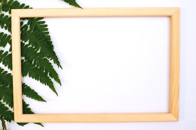 Una romantica composizione di foglie verdi. una foglia di felce verde e una cornice per foto su sfondo bianco. san valentino, pasqua, compleanno, felice festa della donna, festa della mamma. vista dall'alto.