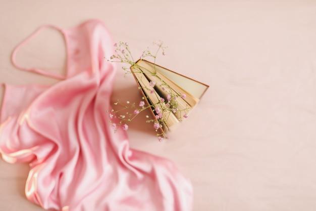 Composizione romantica con fiori a libro e tessuto di seta